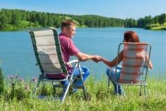 握手的男人和妇女的画象,坐在椅子在湖附近 图库摄影