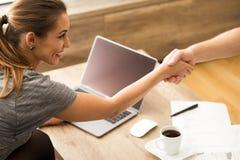 握手的美丽的女商人在工作 免版税库存图片