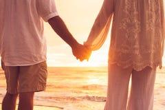 握手的资深夫妇享用在日落 免版税库存图片