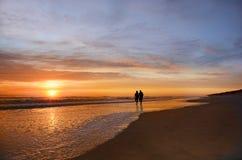 握手的资深夫妇走在享受日出的海滩 免版税库存图片