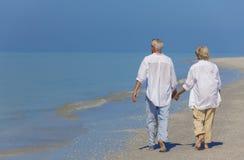 握手的资深夫妇走在海滩 库存图片