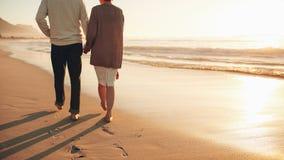 握手的资深夫妇走在海滩 免版税图库摄影
