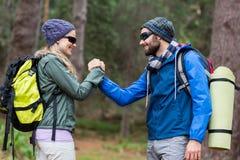 握手的远足者夫妇在森林里 免版税库存图片