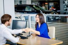 握手的销售主任和女性顾客祝贺在经销权陈列室 免版税库存图片