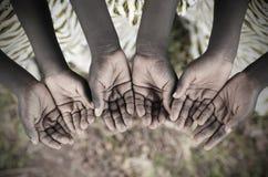 握手的非洲孩子杯乞求帮助 可怜的非洲人 库存照片