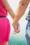 握手的年轻夫妇由海 免版税图库摄影