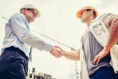 握手的建筑师工程师其他手在建造场所 企业配合,合作,成功collaboratio 图库摄影