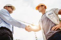 握手的建筑师工程师其他手在建造场所 企业配合,合作,成功collaboratio 免版税库存图片