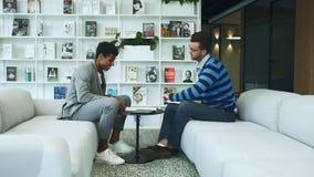 握手的Coworking不同的人 不同种族的正式人侧视图坐在彼此前面的沙发和 影视素材