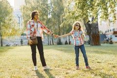 握手走在公园,金黄小时的妈妈和女儿 免版税库存照片