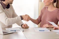 握手,小组会议的年轻微笑的商务伙伴  免版税图库摄影