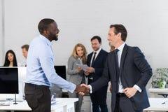握手,握手的商人在会议,在关于合同的商人讨论的前面协议期间  库存图片