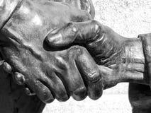 握手,雕象的片段的古铜色会议 免版税库存图片