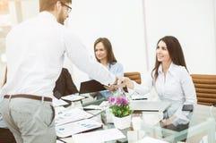 握手经理和客户在一个业务会议上在办公室 库存照片