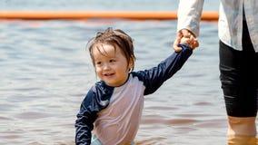 握有他的母亲的小孩男孩手在一个大湖 库存图片