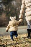握有她的小孩孩子的母亲的背面图手 免版税库存照片