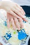 握有婚戒的新娘和新郎手在花束的背景 免版税库存图片