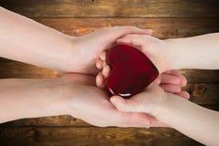 握有心脏的母亲的手婴孩手 图库摄影