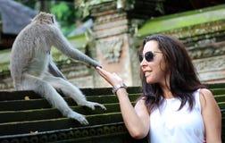 握有猴子的美丽的女孩手在猴子森林在巴厘岛印度尼西亚,有野生动物的俏丽的妇女 库存图片