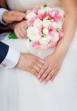 握有花花束的婚礼夫妇手  免版税库存照片