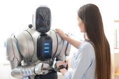握机器人的手的宜人的女孩 免版税图库摄影