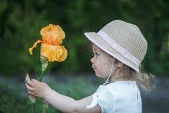 握橙色剑兰的女孩 免版税图库摄影