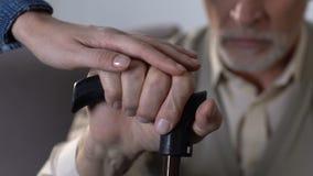 握残疾老人手用拐棍,家庭支持的女儿 影视素材