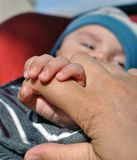 握母亲手指的婴孩 库存图片