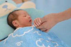 握母亲手的新出生的婴孩 免版税图库摄影