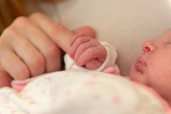 握母亲的手指的星期的婴孩 免版税库存照片