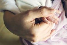 握母亲` s手的婴孩 关心的母性的概念和柔软 特写镜头 免版税库存图片