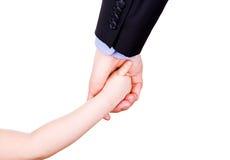 握父亲的手的孩子。 信任、togethterness和支持概念。 免版税图库摄影
