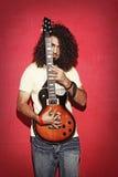 握电吉他美丽的长的卷发的年轻人 免版税库存照片