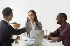 握男性伙伴的手的微笑的女实业家在小组集会 免版税库存照片