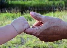 握祖父母手的孩子 免版税库存照片