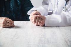 握耐心手的医生在医院 病人护理 免版税库存照片