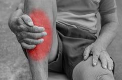握脚和在痛苦区域的老人手按摩脚腕 免版税库存图片