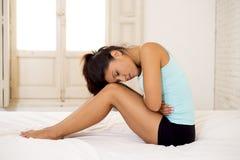 握腹部的年轻美丽的西班牙妇女遭受月经痛苦 免版税库存照片