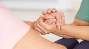 握资深妇女的手的老年医学的护士 免版税库存图片