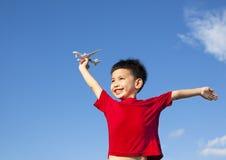 握飞机玩具和开放胳膊的愉快的男孩 免版税库存图片