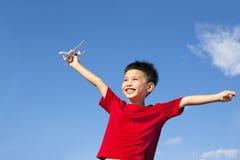 握飞机玩具和开放胳膊的愉快的男孩 免版税库存照片