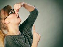 握鼻子的讨厌的女孩 免版税库存照片