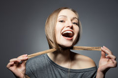 握头发的微笑的妇女 免版税库存图片