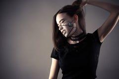 握头发的时兴的计算机国际庞克女孩手中 免版税库存图片