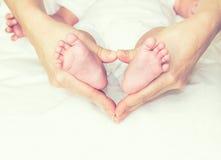 握婴孩的脚的母亲 免版税库存图片