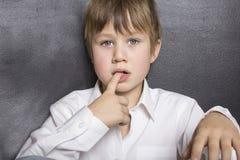握他的在他的嘴的男孩手指 免版税图库摄影