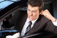 握紧他的拳头的恼怒的年轻人,坐在新的汽车 库存图片