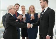 握他的有同事的伙伴的手的成熟商人 库存图片