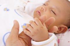 握他的父亲手指的婴孩 免版税库存照片