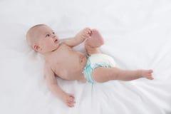 握他的脚的逗人喜爱的男婴 库存照片